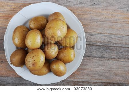 Boiled Potatoes In Their Skins On A Plate, Wooden Background