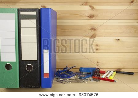 Folders, staplers and hole punches lying on a shelf in the office.