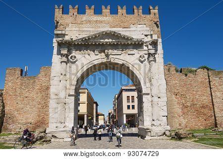 People walk under Augustus Arch in Rimini, Italy.