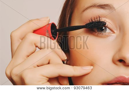 Beautiful young woman applying mascara.