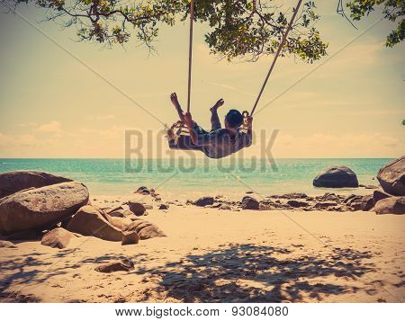 Young Man On Swing At The Beach