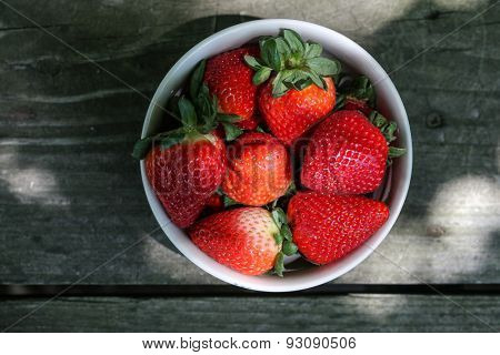 Strawberries in the bowl on wooden table