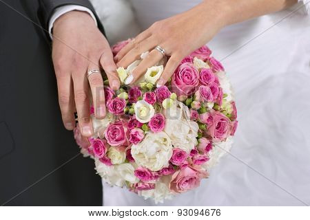 closeup of hands of bride and groom with wedding rings and bouquet