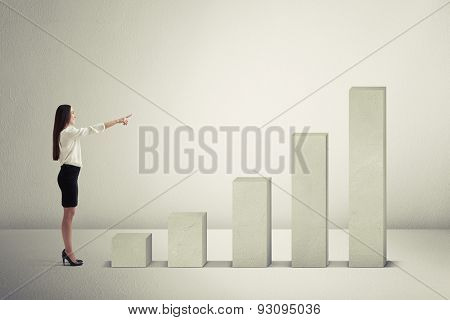 smiley businesswoman pointing at top of concrete diagram