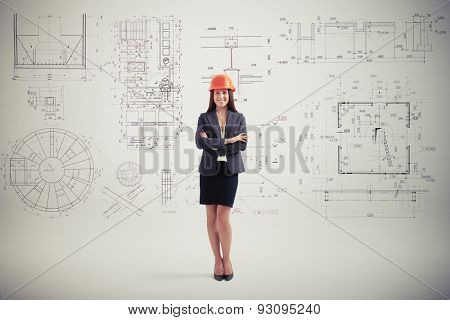 successful woman in hardhat over grey wall with prints
