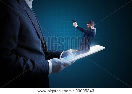 small man with gun got out of the tablet pc and aiming at the big man over dark background. cybercrime concept