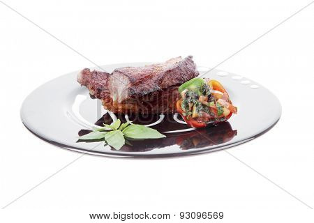 fresh red beef meat steak barbecue garnished vegetable salad sweet potato and basil on black plate isolated over white background