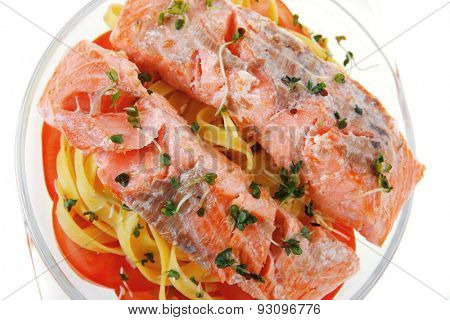 fresh fried natural pink salmon on italian traditional tagliatelle backed with tomato and vegetables isolated over white background