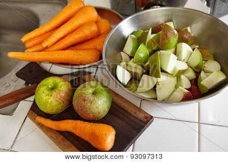 Fresh apple and carrot being prepared to be juiced
