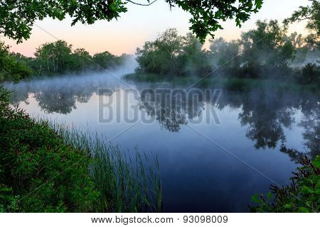 Nice foggy landscape with river at early morning tme