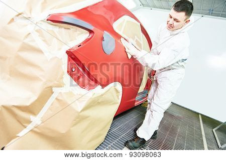 auto mechanic worker wiping car body at automobile repair and renew service station shop in painting chumber