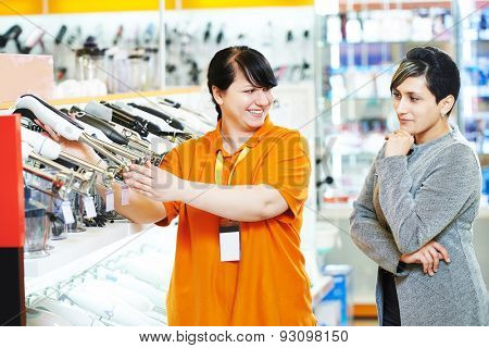 Young woman choosing electric kitchen blender in home appliance shopping mall supermarket