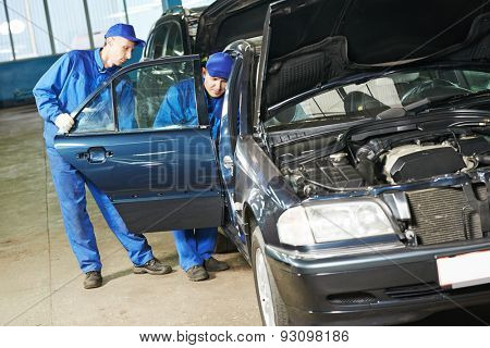 Two repairman mechanics matching automobile body side door on damaged car at repair service station