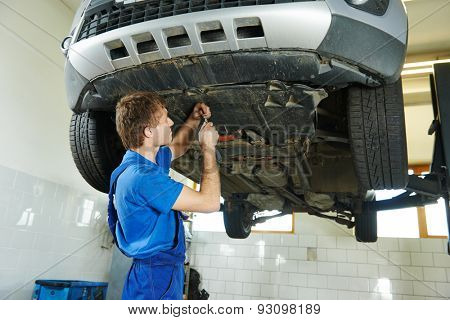 garage auto mechanic repairman assembling bottom car protection during car suspension repair of automobile maintenance at repair service station
