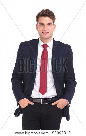 Smiling young business man looking at the camera while holding his hands in pockets.