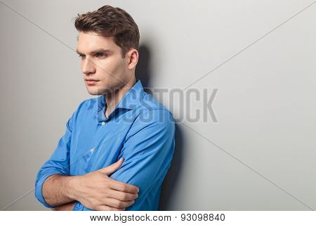 Side view of a young handsome casual man looking away from the camera while leaning on a grey wall.