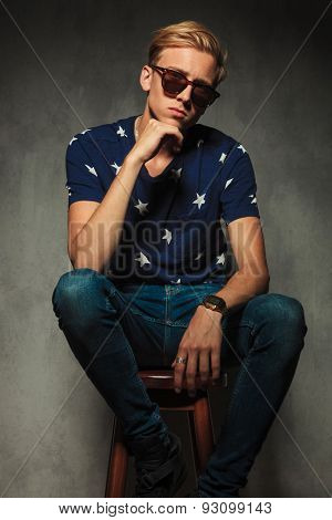 relaxed fashion model is thinking while wearing sunglasses and sitting on a stool