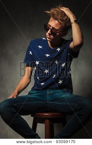 side view of a fashion man fixing his  messy hair while  sitting on a stool in studio