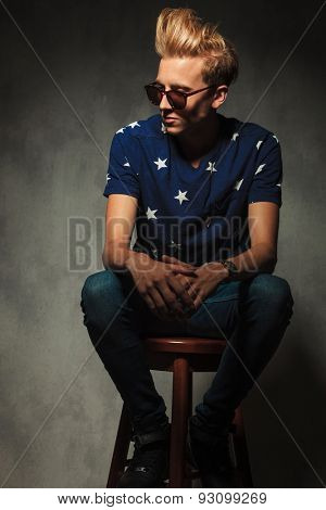 young fashion man is resting on a stool and looks away from the camera in studio