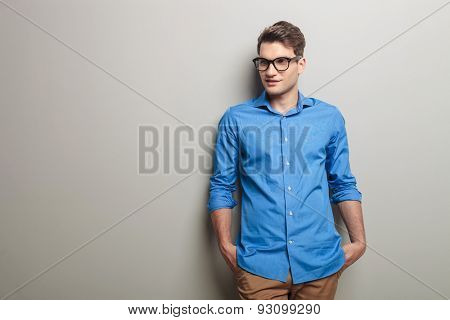 Handsome fashion man leaning on a grey wall while holding his hands in pockets.