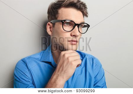 Portrait of a handsome young man wearing black glasses, looking away from the camera.