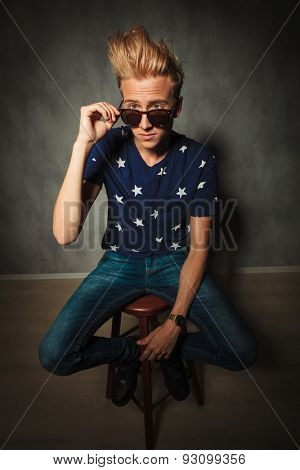 cool fashion model is taking off his sunglasses and sits on a chair in studio