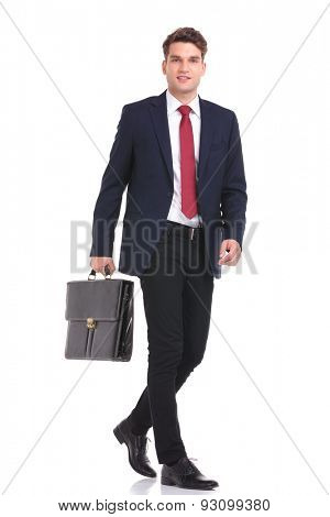 Side view of a young business man holding a brief case while walking on isoaed background.