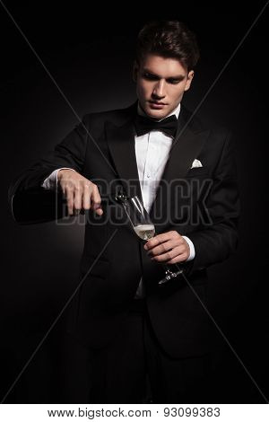 Young elegant man pouring wine in a glass while looking down.