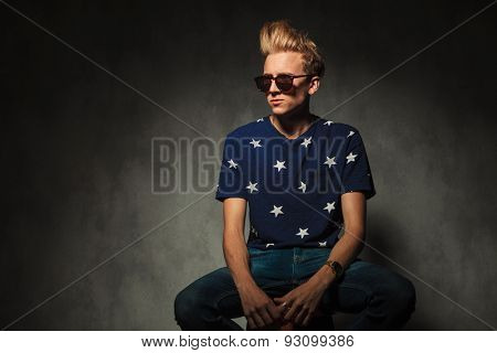 cool fashion model with sunglasses sitting on a stool and looks away from the camera to a side