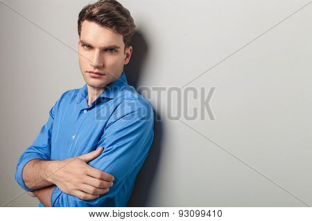 Side view of a handsome young man leaning on a grey wall holding his hands crossed.