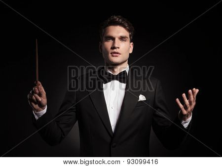 Young handsome man conducting an orchestra.
