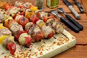 stock photo of braai  - BBQ Grilled Mixed With Vegetables Pork Kebabs On The Wooden Cutting Board - JPG