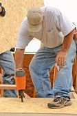 stock photo of rafters  - Framing contractor installing roof sheeting over rafters on a new commercial residential construction project - JPG