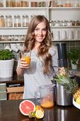 foto of juicer  - Happy pretty woman making fresh healthy juice with juicer - JPG