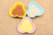 stock photo of millet  - Closeup of buckwheat groats barley groats and millet groats in colorful bowl lying on jute canvas healthy food and healthy nutrition - JPG