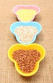 picture of millet  - Closeup of buckwheat groats barley groats and millet groats in colorful bowl lying on jute canvas healthy food and healthy nutrition - JPG