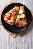 foto of crepes  - homemade crepes with fresh strawberries bananas and cream on a plate - JPG