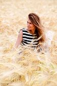 stock photo of dry grass  - gorgeous girl walking in the field of long grass and dragging her hand touching the dry grass while laughing and smiling carefree healthy lifestyle - JPG