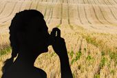 stock photo of inhalant  - Woman using inhaler for asthma against rural fields - JPG