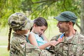 stock photo of reunited  - Army parents reunited with their daughter on a sunny day - JPG