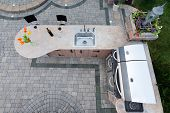 stock photo of paving  - Outdoor summer kitchen with a built in gas barbecue and sink in a cement counter top in a corner of a brick paved patio for healthy living view from above - JPG