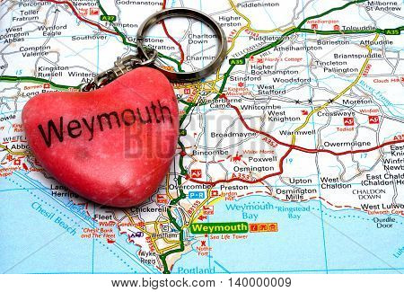 WEYMOUTH, UNITED KINGDOM - JULY 24, 2016 - Pink stone Weymouth keyring on a map Weymouth Dorset England UK Western Europe, July 24, 2016.