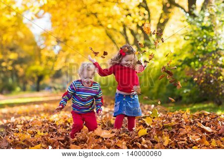 Happy children playing in beautiful autumn park on warm sunny fall day. Kids play with golden maple leaves. Focus on girl
