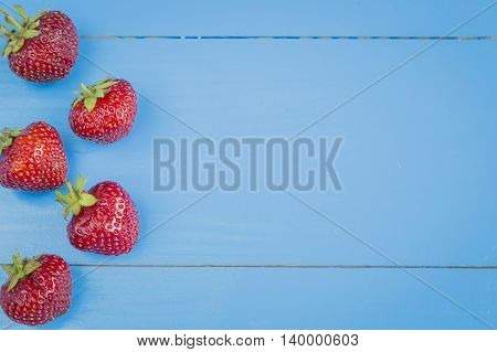 Fresh strawberries in a line on blue wooden background, copyspase