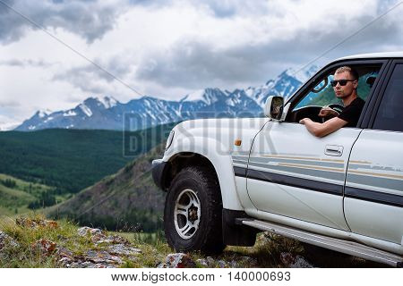 man with glasses in the SUV drove to the edge of the mountains