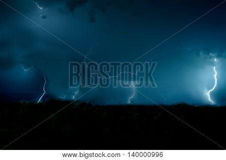 Magical storm passing over the forest at night