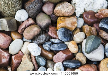 Background of marine pebbles, different shapes and colors