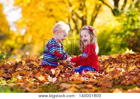 Happy children playing in beautiful autumn park on warm sunny fall day. Kids play with golden maple leaves.