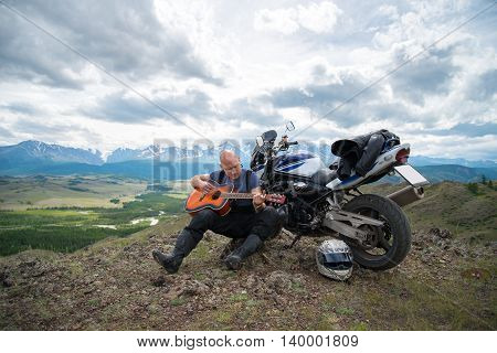bald motorcyclist plays guitar sitting on a motorcycle on the background of mountains