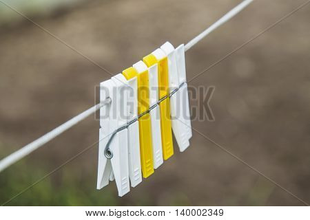 Two colorful clothespin white and yellow on the white rope
